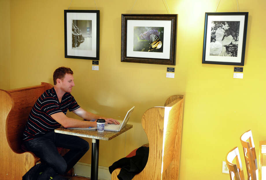 Art and photography made by local artists are on display at Cafe Atlantique in Milford, Conn. on Thursday January 9, 2014. Enjoying a coffee while getting some work done is Milford resident Adam Zona. Photo: Christian Abraham / Connecticut Post