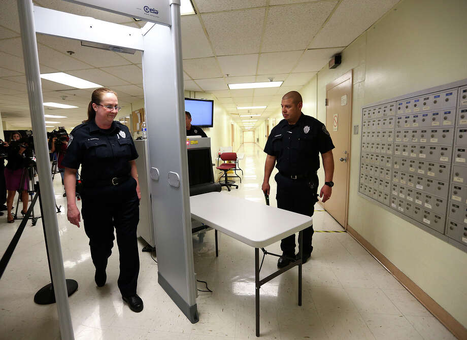 Bexar County Deputy Saundra Martinez goes through a detector as Deputy Francisco Gonzalez prepares to wand her at the entrance to the secure area of the Bexar County Jail, Thursday, Jan. 9, 2014. Besides the new security feature implemented Monday, Sheriff Susan Pamerleau announced the termination of two jailers for violating administrative policies that prohibit a cellphone in a secure location and, in an unrelated investigation, charges brought against four people for smuggling or having a phone in the jail. Photo: Jerry Lara, San Antonio Express-News / ©2013 San Antonio Express-News