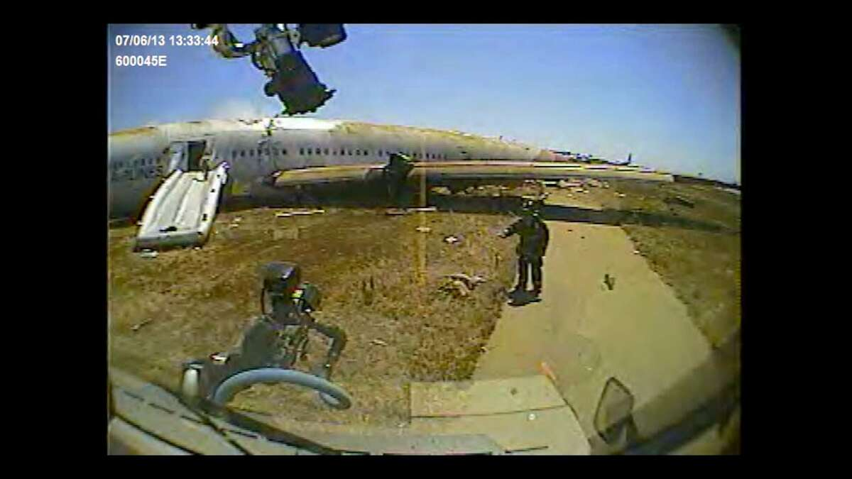 San Francisco firefighter Roger Phillips directs a fire rig around Ye Meng Yuan after the July 6,2013 crash of an Asiana Airlines jet at San Francisco International Airport. Firefighters had concluded that the 16-year-old Chinese girl was dead, although the San Mateo County coroner later said she was alive when the rig?•s dashboard camera filmed this image.