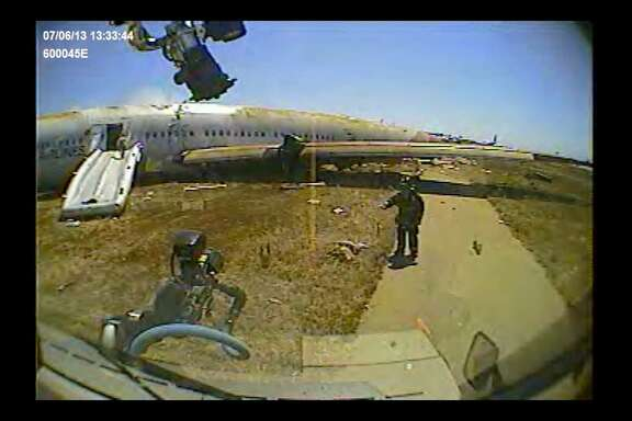 San Francisco firefighter Roger Phillips directs a fire rig around Ye Meng Yuan after the July 6,2013 crash of an Asiana Airlines jet at San Francisco International Airport. Firefighters had concluded that the 16-year-old Chinese girl was dead, although the San Mateo County coroner later said she was alive when the rigÕs dashboard camera filmed this image.