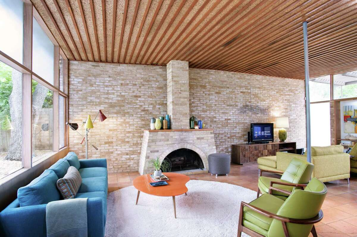 The living areas of the midcentury modern home are open and light. Cork ceilings and a fireplace made from local brick contribute to its handcrafted aura.