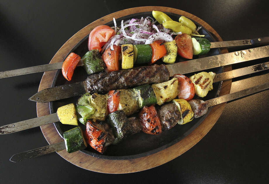 A sizzling platter of chicken, lamb and kefta kebabs, with an assortment of vegetables, are part of the family dinner. Photo: Photos By Tom Reel / San Antonio Express-News