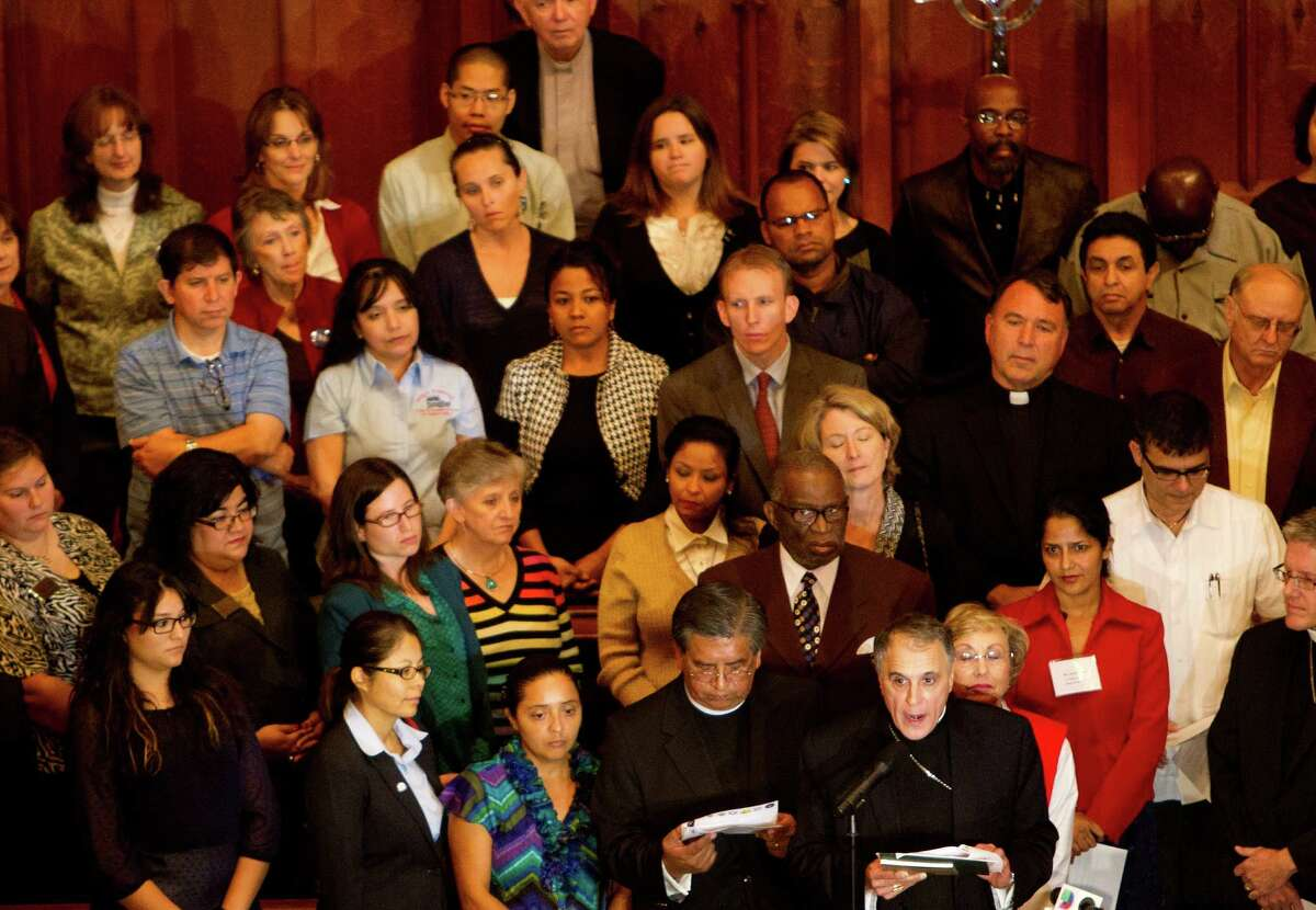 Cardinal Daniel N. DiNardo, bottom right, speaks during a press conference at St Paul's United Methodist Church urging the House of Representatives to pass comprehensive immigration reform, Wednesday, Oct. 23, 2013, in Houston. Individuals from The Metropolitan Organization (TMO) and members of an Interfaith coalition of Houston area religious leaders urged congress to keep families together, protect workers and