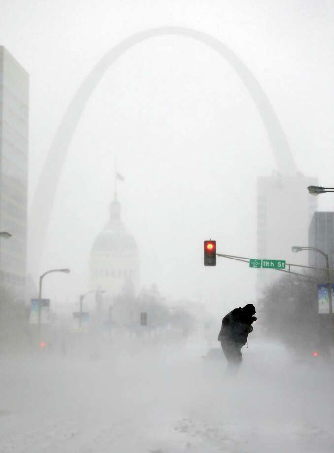 FILE - In this Sunday, Jan. 5, 2014, file photo, a person struggles to cross a street in blowing and falling snow as the Gateway Arch appears in the distance, in St. Louis. The deep freeze that gripped much of the nation this week wasn't unprecedented, but with global warming we're getting far fewer bitter cold spells, and many of us have forgotten how frigid winter used to be. (AP Photo/Jeff Roberson, File) ORG XMIT: NYSB201 Photo: Jeff Roberson / AP