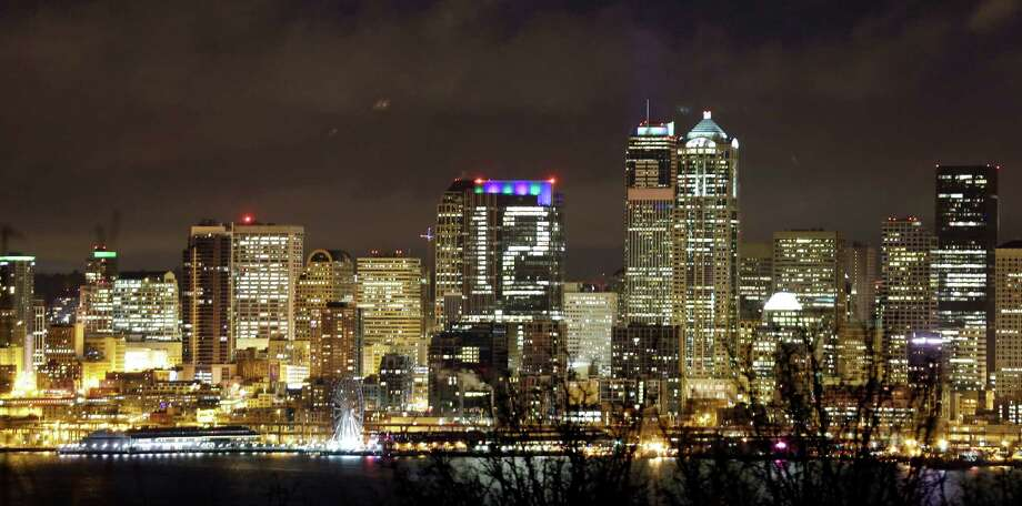 "Lights on a downtown Seattle building form a giant figure ""12"" in honor of Seattle Seahawks fans and the team's success Wednesday, Jan. 8, 2014, in Seattle. The Russell Investments Center, at 1301 Second Ave., coordinated with building tenants to strategically close window blinds to light the number twelve, honoring the team's ""12th Man,"" on the west-facing side of the 42-story building on Wednesday. The Seahawks play the New Orleans Saints Saturday in an NFC divisional playoff game. Photo: Elaine Thompson, AP / AP"