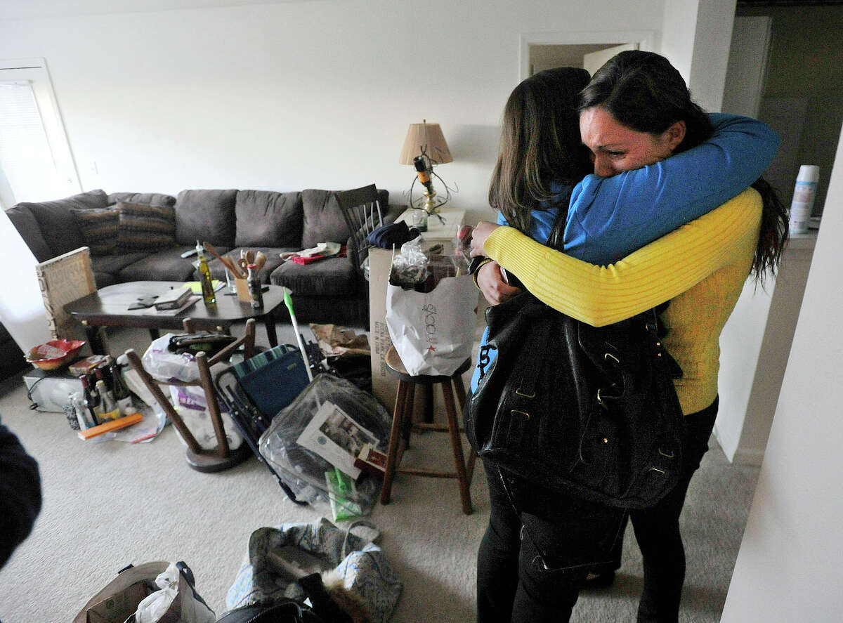 Kat Fairchild, right, hugs her neighbor, Nicole Bott, in Fairchild's apartment in Avalon Stamford Harbor in Stamford, Conn., on Thursday, Jan. 9, 2014. Last Saturday, a water line for the sprinkler system broke on the fourth floor above Fairchild's apartment on the second floor damaging her living space along with others.