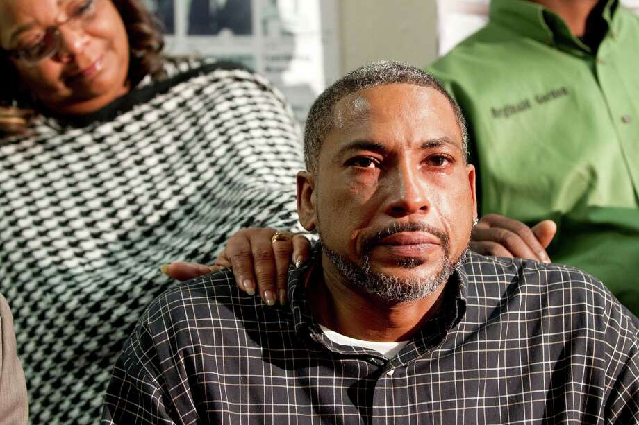 Reginald Matthews is comforted by supporters during a press conference Thursday at the Forward Times newspaper. Photo: Johnny Hanson, Staff / © 2014  Houston Chronicle