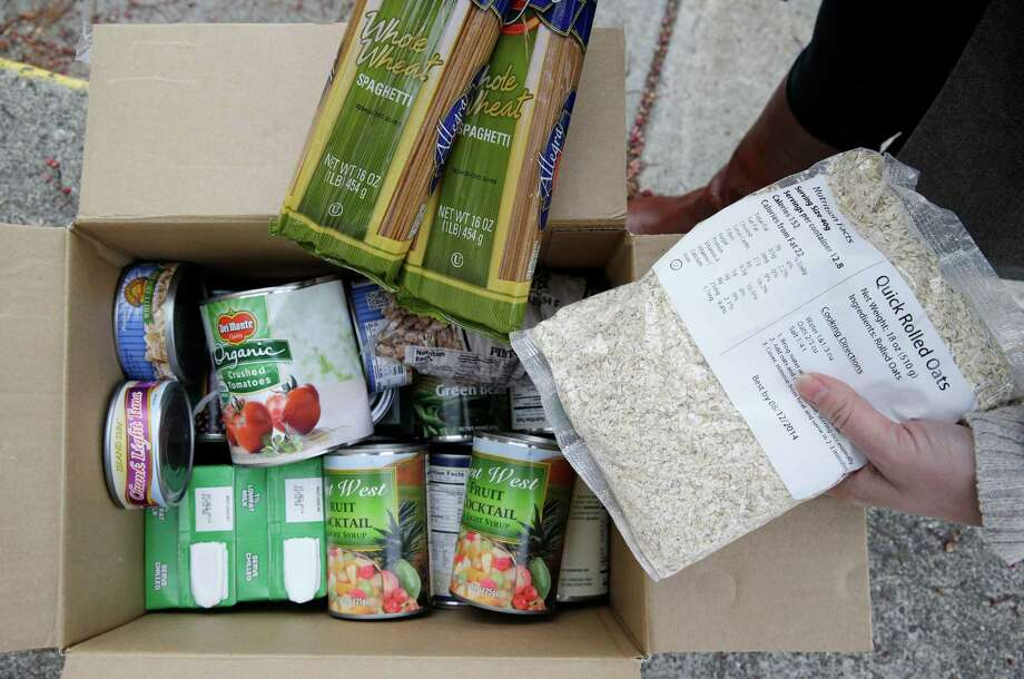 This photo taken Jan. 8, 2014 shows the contents of a specially prepared box of food at a food bank distribution in Petaluma, Calif., part of a research project with Feeding America to try to improve the health of diabetics in food-insecure families. Doctors are warning that the federal government could be socked with a bigger health bill if Congress cuts food stamps _ maybe not immediately, they say, but if the poor wind up in doctors' offices or hospitals as a result. (AP Photo/Eric Risberg) ORG XMIT: WX303 Photo: Eric Risberg / AP