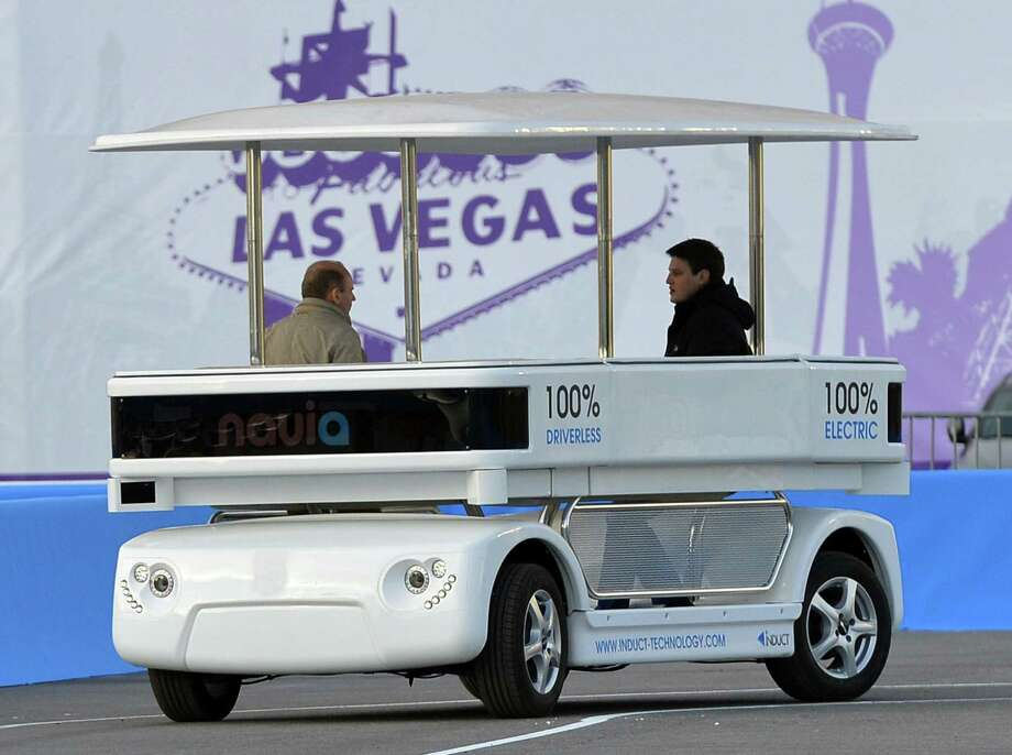Induct Technology demonstrates the Navia, a laser-guided, electric-powered, eight-passenger shuttle that looks like a big golf cart, at the International Consumer Electronics Show in Las Vegas on Monday. Photo: Jack Dempsey / Associated Press / FR42408 AP