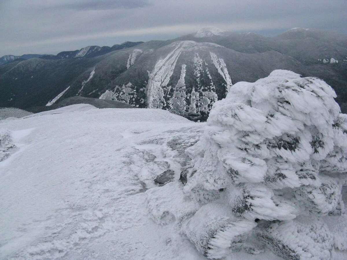 The summit cairn on Iroquois with Mt. Colden and Mt. Marcy in the distance.Read about this hike.