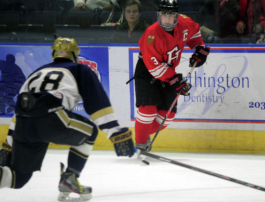 Fairfield Prep's Matt Wikman moves the puck as Notre Dame of Fairfield's Mark Russo intercepts, during boys hockey action at the Webster Bank Arena in Bridgeport, Conn. on Thursday January 9, 2014. Photo: Christian Abraham / Connecticut Post