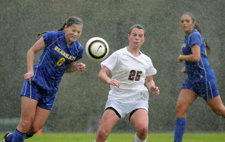 Thursday's rain bogged down Klein and The Woodlands, but defender Katie Neary (6) and the Bearkats topped midfielder Mollie Bond (25) and the Highlanders. Photo: Jerry Baker, Freelance