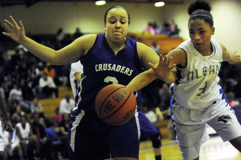 Catholic Central's Sarina Schwing, left, and Albany's Ayanna Hunter chase a loose ball during their