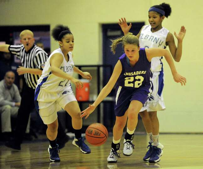 Catholic Central's Madison Purcell, center, controls the ball as Albany's Kiersten Gordon, left, and