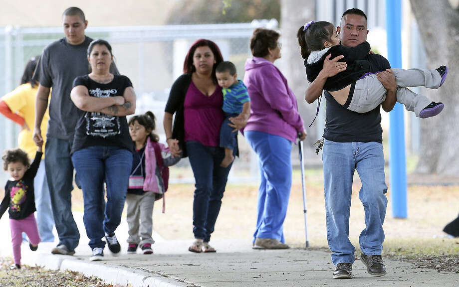Parents bring their children out of Carroll Early Childhood Education Center after they were under precaut- ionary lockdown after school hours during a police operation at a nearby house in the 100 block of Schumacher Road. Photo: Tom Reel / San Antonio Express-News