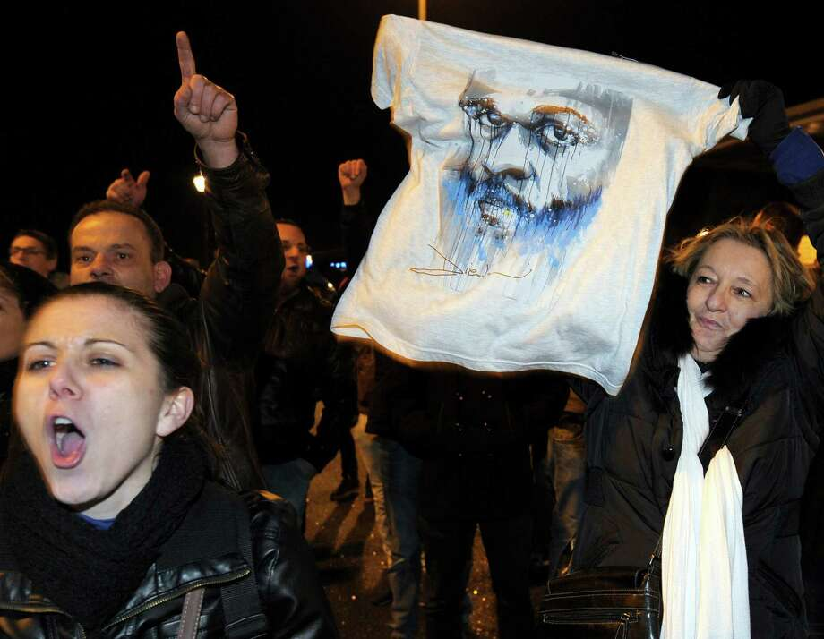 A woman holds a shirt depicting controversial French humorist Dieudonne as people gather in front of the Zenith theater in Nantes, France, after his performance was canceled. Photo: Jean-Sebastien Evrard / AFP / Getty Images / AFP
