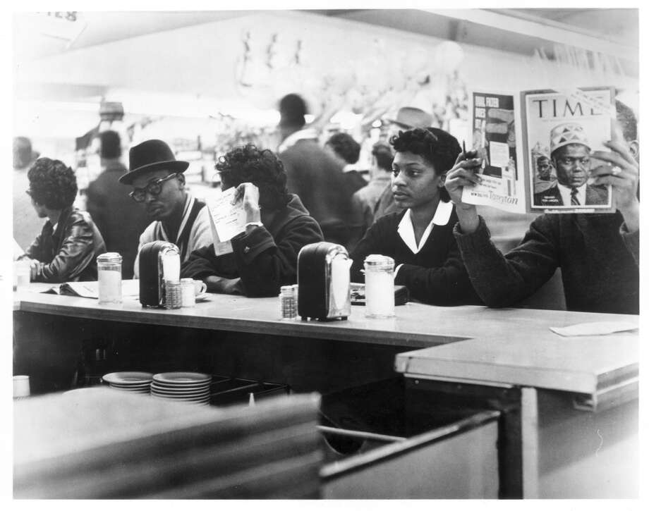 March 4, 1960 sit-in at Weingarten's supermarket. These were TSU students. Harold L. Stovall is wearing glasses and hat. Halcyon Sadberry Watkins, shown on right, was a 20-year-old TSU student when she sat at the counter. Pete Hogrobrooks is reading Time magazine at the far right. (Staff | Houston Post)