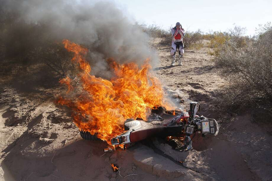 Honda rider Paulo Goncalves of Portugal, right, reacts as he sees his motorcycle on fire during the fifth stage of the Dakar Rally between the cities of Chilecito and Tucuman in San Miguel de Tucuman, Argentina, Thursday, Jan. 9, 2014. (AP Photo/Victor R. Caivano) Photo: Victor R. Caivano, Associated Press