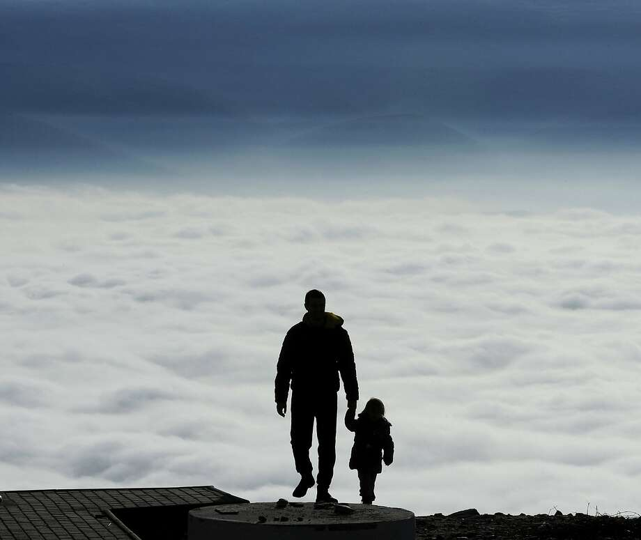 A man with a child walks towards the top of Vodno Mountain in Skopje, Macedonia, Thursday, Jan. 9, 2014.  Weather forecasts predict ongoing sunny weather on the mountains with mild temperatures and fog in the lowlands and valleys. (AP Photo/Boris Grdanoski) Photo: Boris Grdanoski, Associated Press