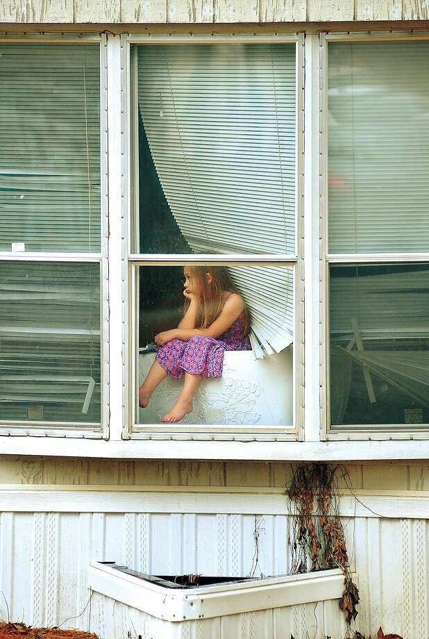 A young girl looks through a window on Thursday, Jan. 9, 2014, at the scene of an officer-involved shooting in Jonesboro, Ark., where reports of one person was killed and two injured. (AP Photo/The Jonesboro Sun, Rob Holt) Photo: Rob Holt, Associated Press