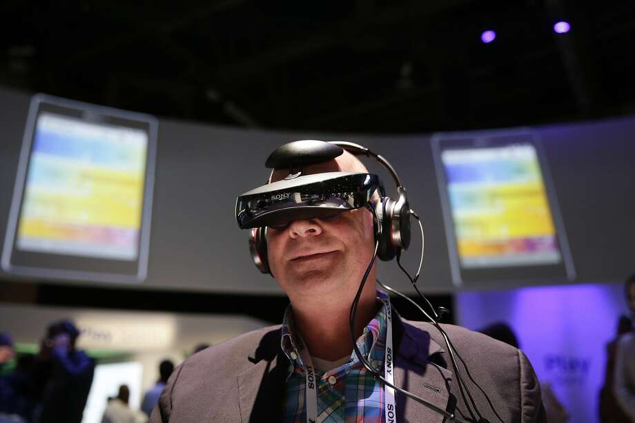 Juergen Boyny, of Germany, watches a video clip with a personal viewing device at the Sony booth at the International Consumer Electronics Show(CES) on Thursday, Jan. 9, 2014, in Las Vegas. (AP Photo/Jae C. Hong) Photo: Jae C. Hong, Associated Press