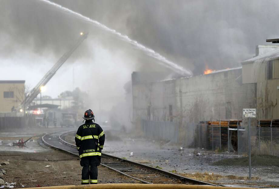 A firefighter monitors a five-alarm warehouse fire on Thursday, Jan. 9, 2014, in San Jose, Calif. The fire consumed a 120,000 square foot warehouse and caused traffic delays, evacuation of homes and the closing of a nearby school. (AP Photo/Marcio Jose Sanchez) Photo: Marcio Jose Sanchez, Associated Press