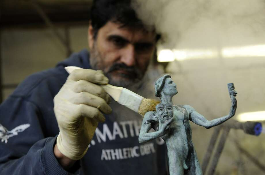 Ricardo Godinez of American Fine Arts Foundry brushes debris off a freshly made Actor, the Screen Actors Guild Award, on Thursday, Jan. 9, 2014, in Burbank, Calif. The Screen Actors Guild will be held on Sunday, Jan. 18, in Los Angeles. (Photo by Chris Pizzello/Invision/AP) Photo: Chris Pizzello, Associated Press