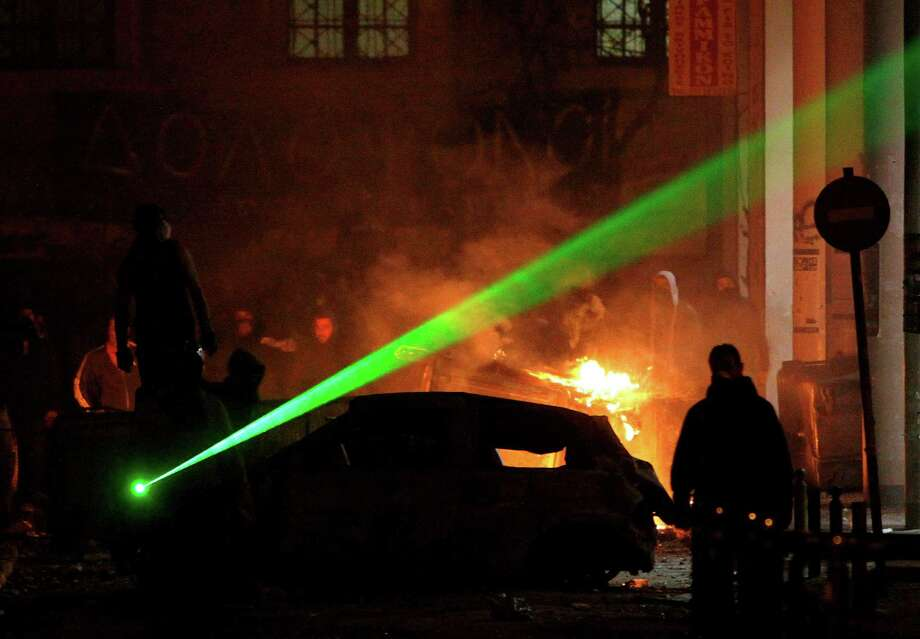 Green lasers can endanger others; blue lasers are strong enough to cause permanent vision loss. In this file photo, protesters in Athens throw stones at riot police during clashes in Athens. Photo: Petros Karadjias, STF / AP