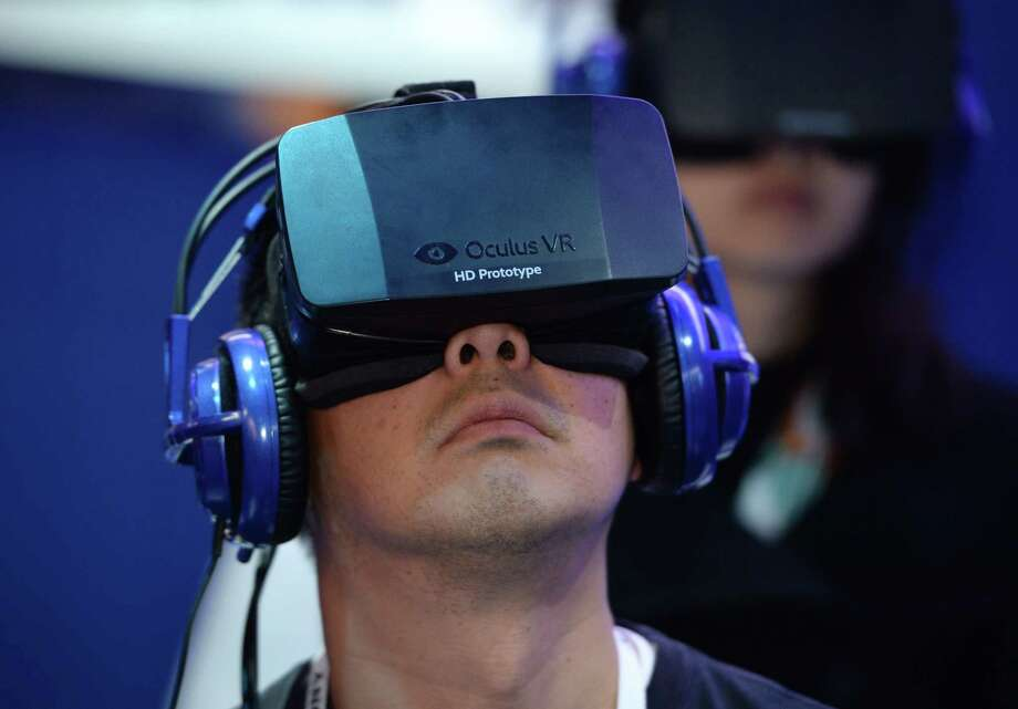 An attendee wears an Oculus Rift HD virtual reality head-mounted display at he plays EVE: Valkyrie, a multiplayer virtual reality dogfighting shooter game, at the Intel booth. Photo: ROBYN BECK, Getty Images / AFP