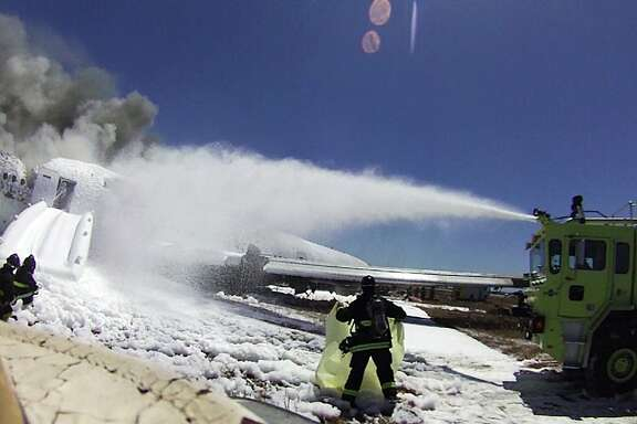 This photo provided by the San Francisco Chronicle shows an image from the helmet-mounted video camera of a San Francisco fire battalion chief at the scene of the crash of Asiana Flight 214 shows a firefighter covering the body of passenger Ye Meng Yuan at San Francisco International Airport on July 6, 2013 in San Francisco, Calif. (AP Photo/San Francisco Chronicle)