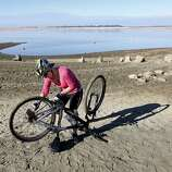 Monica Soares fixes the chain on her bicycle on part of the dry lake bed at Folsom Lake near Folsom, Calif., Thursday Jan. 9, 2014.  Reservoirs in the state have dipped to historic lows after one of the driest calendar years on record.  While still more than 100 yards from the waters edge, Soares is in a spot usually covered in water.