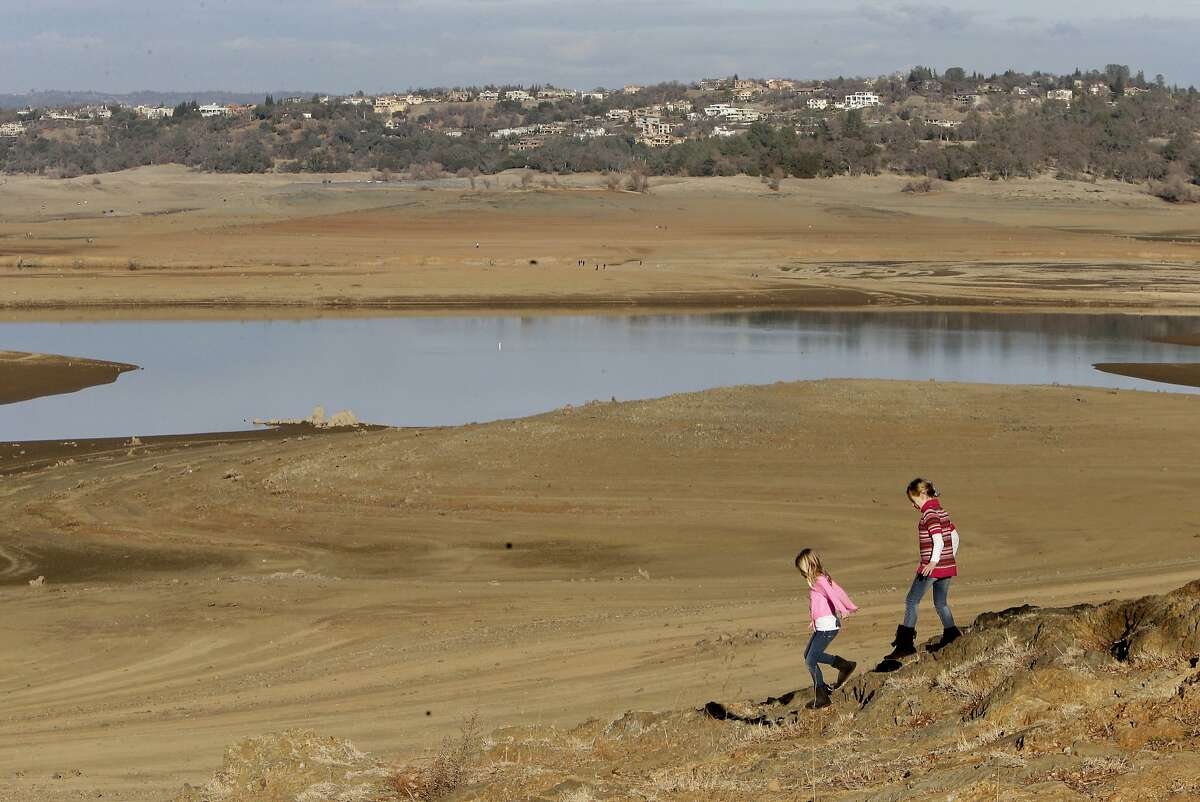 With the edge of Folsom Lake, Calif., more than 100 yards away, Gina, 8, left, and Sydney, 9, Gerety walk on rocks that are usually at the waters edge, Thursday Jan. 9, 2014. Gov. Jerry Brown officially declared a drought emergency in California, as the state faces a serious water shortage. Reservoirs in the state have dipped to historic lows after one of the driest calendar years on record.