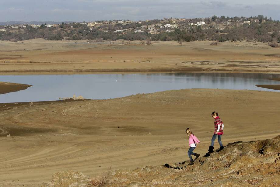 With the edge of Folsom Lake, Calif.,  more than 100 yards away, Gina, 8, left, and Sydney, 9, Gerety walk on rocks that are usually at the waters edge,  Thursday Jan. 9, 2014.  Gov. Jerry Brown officially declared a drought emergency in California, as the state faces a serious water shortage. Reservoirs in the state have dipped to historic lows after one of the driest calendar years on record. Photo: Rich Pedroncelli, Associated Press