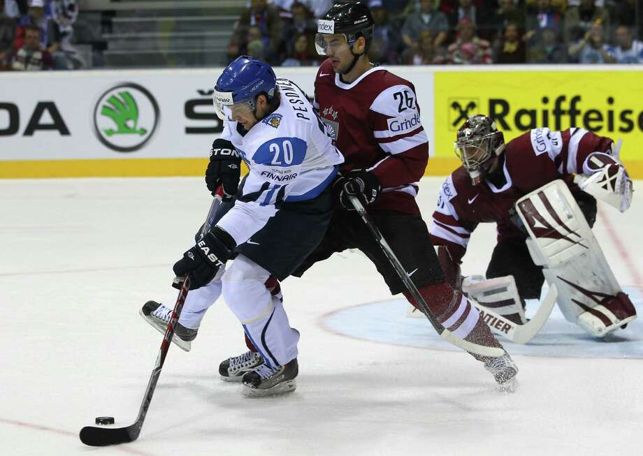 Krisjanis Redlihs (R) of Latvia, seen here battling and Janne Pesonen (L) of Finland for the puck during the IIHF World Championship group D match between Latvia and Finland at Orange Arena on May 2, 2011 in Bratislava, Slovakia, will play on Latvia's Olympic team in Sochi. Redlihs played for the River Rats between 2002-2006. Photo: Martin Rose, Bongarts/Getty Images / 2011 Getty Images