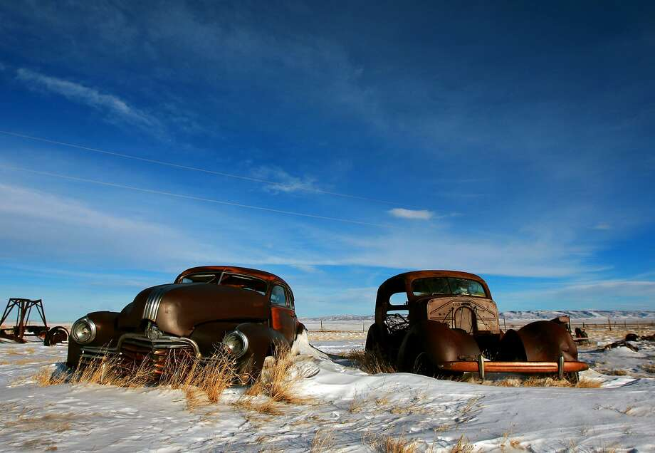 Rust buckets of yesteryear:A pair of 1940s-vintage cars sit in a field along U.S. 30/287 in the largely abandoned 