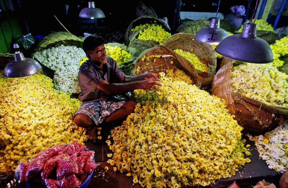 Business is blooming: An Indian flower vendor waits for customers at a market in Chennai. Hindus often offer fresh flowers to deities as a 