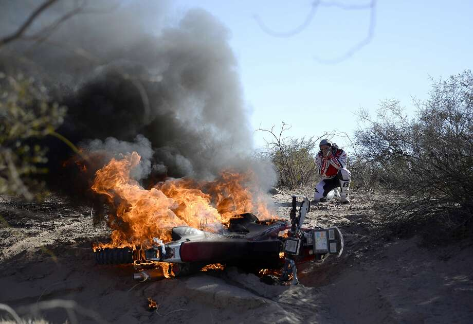 Hopes for victory go up in smoke: Portuguese motorcyclist Paulo Goncalves holds his head in his hands as his Honda burns during Stage 5 of the Dakar 2014 rally between Chilecito and Tucuman, Argentina. Goncalves says he was riding over sand and dry vegetation when he noticed his feet were getting hot. By the time he stopped and jumped off, his motorcycle was engulfed in flame, and he was unable to extinguish the fire. Photo: Franck Fife, AFP/Getty Images