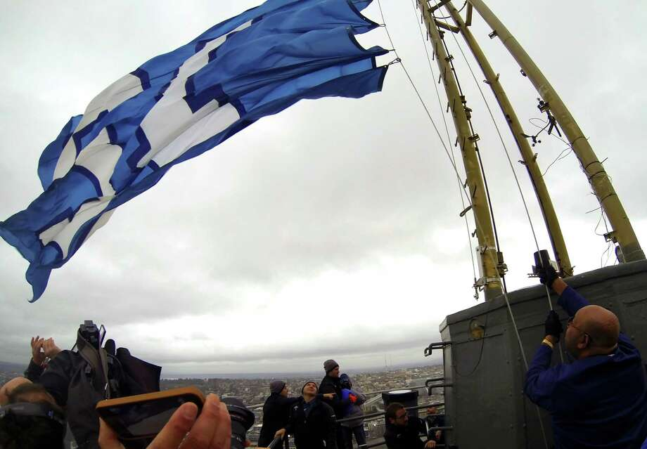 """Cortez Kennedy, lower right, former NFL Seahawks defensive tackle and Pro Football Hall of Fame player, raises the """"12th Man"""" flag at the height of the Space Needle in celebration of the Seahawks upcoming playoffs Friday, Jan. 10, 2014, in Seattle. The flag will remain up until Sunday night. Photo: JORDAN STEAD, SEATTLEPI.COM / SEATTLEPI.COM"""