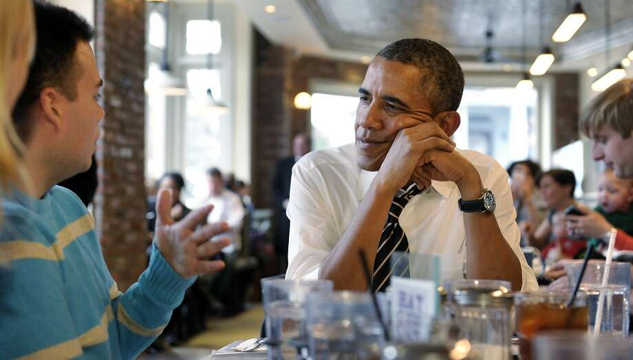 President Barack Obama listens to Andres Cruz, left, as he has lunch with five young people at The Coupe restaurant in the Columbia Heights section of Washington, Friday, Jan. 10, 2014. The five are spearheading creative outreach efforts to connect with and help enroll young consumers through the Marketplaces or are interested in getting more involved with these efforts. (AP Photo/Susan Walsh) Photo: Susan Walsh, Associated Press