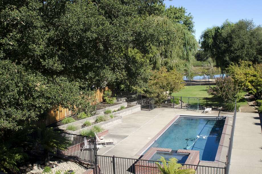 The backyard includes mature landscaping, with a pool with a retractable cover, spa, level grass pad and white sand beach on the Mokelumne River. Photo: Alicia Crosson Photography