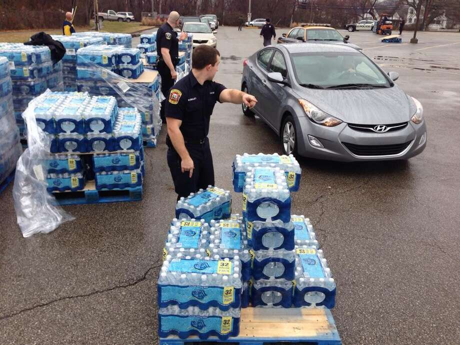 Police direct traffic through a water distribution site set up Friday at a recreation center in South Charleston, W.Va., after a chemical spill into the Elk River. Photo: Marcus Constantino, MBO / The Daily Mail