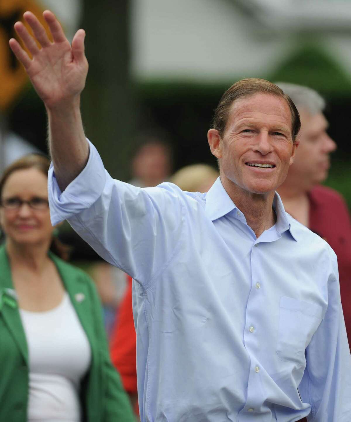 """U.S. Sen. Richard Blumenthal waves to the crowd while walking in the 52nd Annual Newtown Labor Day Parade in Newtown, Conn. on Monday, Sept. 2, 2013. About 100 floats and groups participated in the parade, themed """"We are Newtown - marching strong."""""""