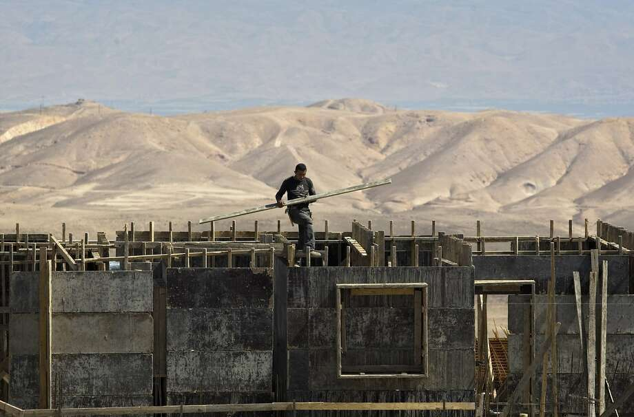 A Palestinian works at a construction site in the Jewish West Bank settlement of Maale Adumim. Photo: Sebastian Scheiner, AP