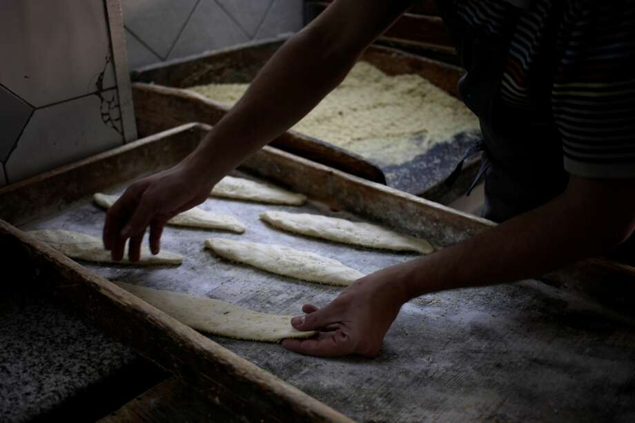 Jordan: A baker organizes pieces of dough for Kaek bread on a wooden tray before baking it at the Salah al-Deen bakery in Amman. The self-service bakery was established by Mahmoud Darraj, who died eight years ago. He was a Palestinian baker who came from Jerusalem to Amman in 1965, two years before the 1967 Middle East war, bringing with him a famous Palestinian traditional bread meal, which called Kaek, covered with roasted sesame seeds and provided with cheese, boiled eggs and thyme. He opened the store 24 hours a day and 7 days a week, and became his bakery's signature food. Photo: Mohammad Hannon, Associated Press