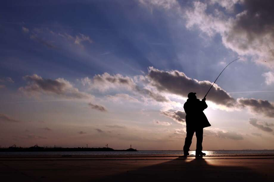 Greece: A fisherman casts his line at the sea front area of Faliro coast near Athens, Greece, at sunset. Photo: Kostas Tsironis, Associated Press