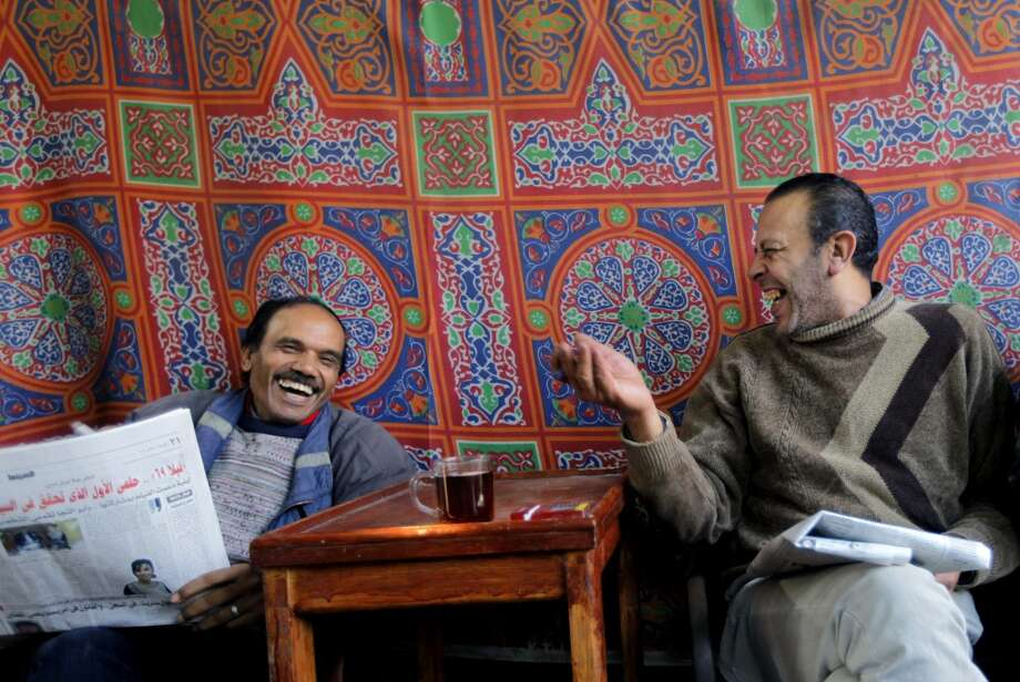 Egypt: Men speak as they read their newspapers at a coffee shop in Cairo, Egypt. Photo: Amr Nabil, Associated Press