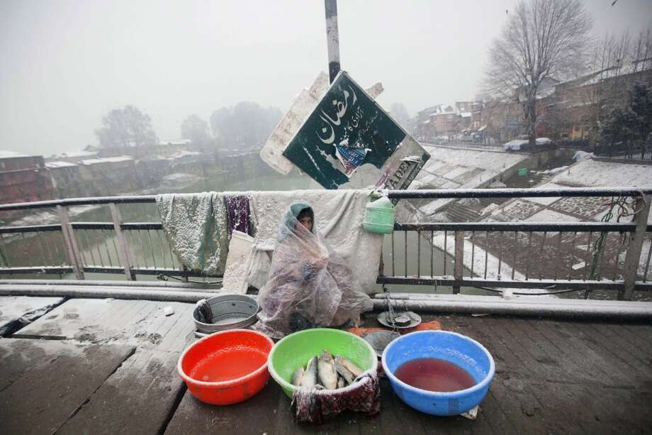 India: A Kashmiri street food vendor sits wrapped in a plastic sheet while waiting for customers as fresh snow falls in Srinagar, India. Photo: Dar Yasin, Associated Press