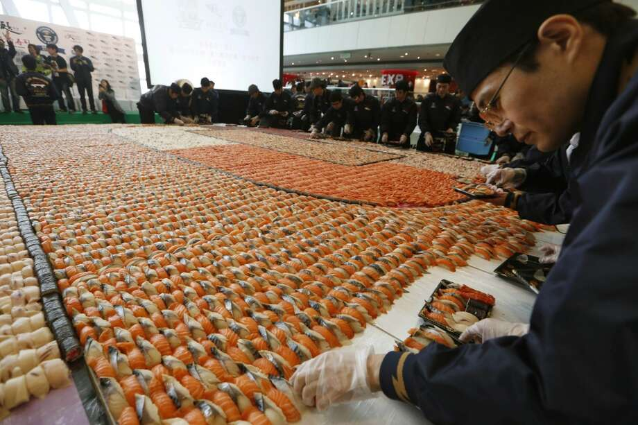 Hong Kong: Staff members from a Japanese sushi chain restaurant pack sushi boxes after creating a sushi mosaic to mark the 10th anniversary of the restaurant at a shopping mall in Hong Kong. A total of 20,647 pieces of sushi were formed into a 37.16-square-meter (400-square-foot) space which broke the Guinness World Records of the largest sushi mosaic. Photo: Kin Cheung, Associated Press