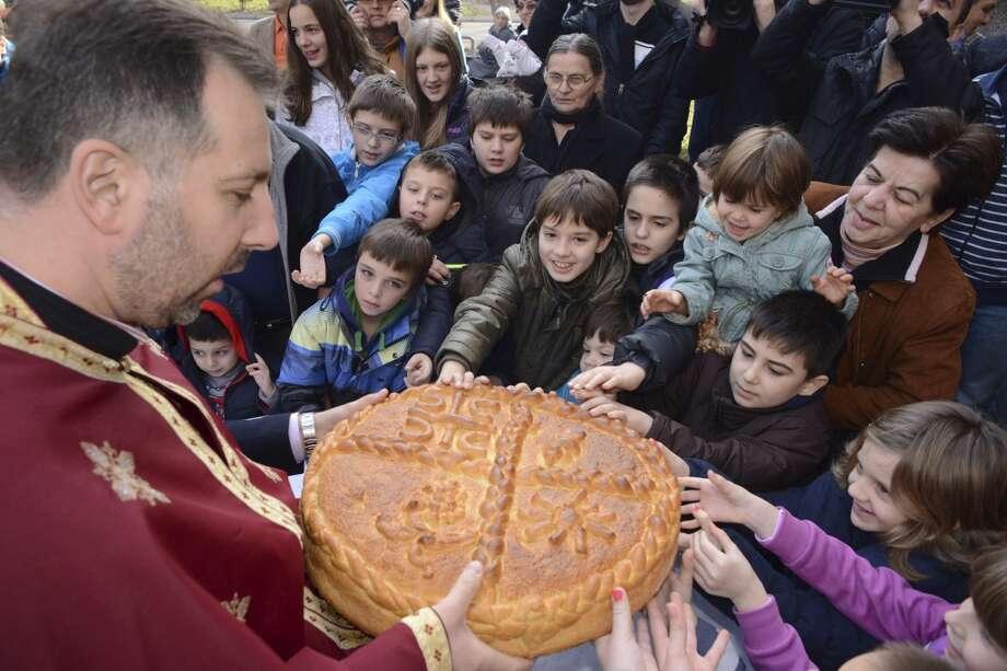 Bosnia: Bosnian Serb children break the traditional Christmas bread to mark Orthodox Christmas Day festivities  in Bosnian  town of Banja Luka, 250 km northwest of Sarajevo, on Tuesday, Jan. 7, 2014. Bosnian Serbs as Orthodox Christians celebrates Christmas on Jan. 7, according to the old calendar. Photo: Radivoje Pavicic, Associated Press
