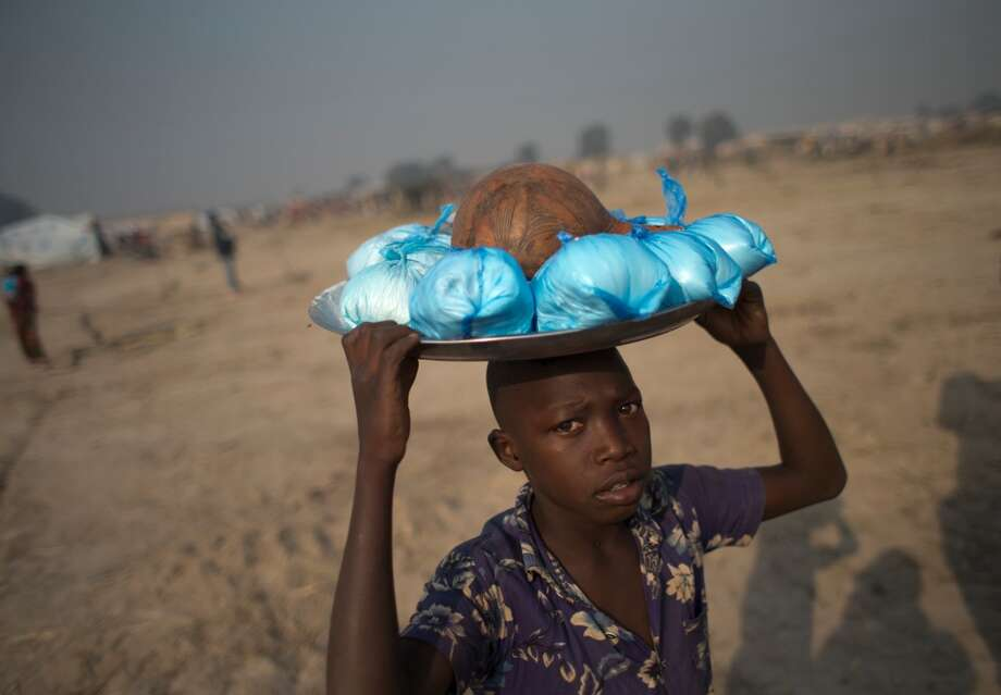 Central African Republic: A boy carries bags of corn meal to sell inside an informal camp housing an estimated 100,000 displaced people. Photo: Rebecca Blackwell, Associated Press